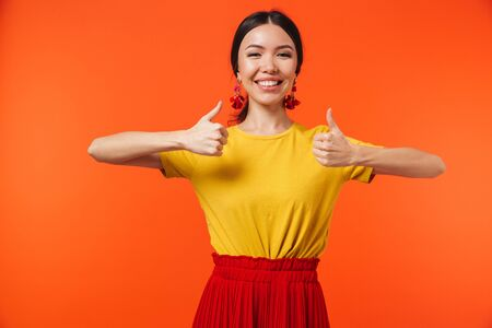 Foto de Image of a beautiful excited happy young woman posing isolated over orange wall background make thumbs up gesture. - Imagen libre de derechos