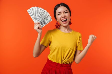 Photo pour Image of beautiful hispanic woman 20s dressed in skirt smiling while holding bunch of money bills isolated over red background - image libre de droit