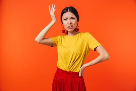 Photo for Image of a beautiful confused displeased young woman posing isolated over orange wall background. - Royalty Free Image
