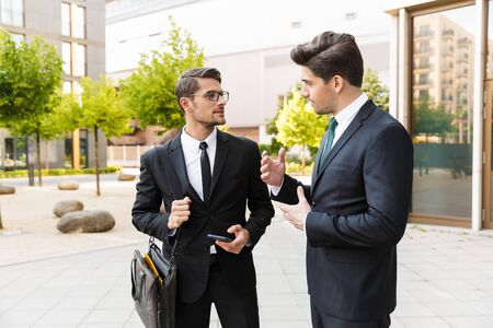 Photo pour Two attractive confident young businessmen wearing suits standing outdoors at the city streets, discussing new project - image libre de droit