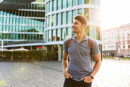 Photo pour Handsome smiling young man dressed casually spending time outdoors at the city, carrying backpack - image libre de droit