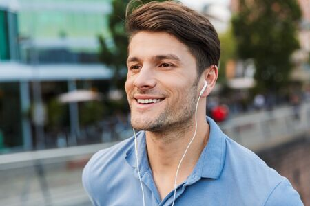 Photo pour Handsome smiling young man dressed casually spending time outdoors at the city, listening to music with earphones - image libre de droit