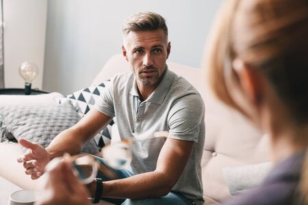 Photo pour Photo of brooding handsome man having conversation with psychologist on therapy session in room - image libre de droit