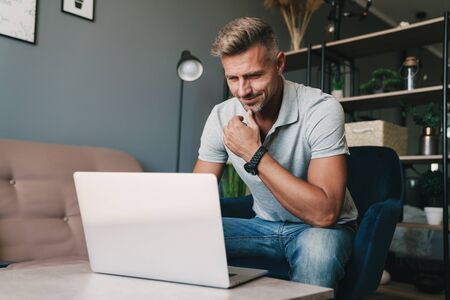 Photo pour Photo of successful caucasian man in casual clothing using laptop while sitting on armchair at home - image libre de droit