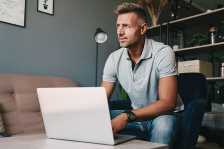 Photo pour Photo of concentrated caucasian man in casual clothing using laptop while sitting on armchair at home - image libre de droit