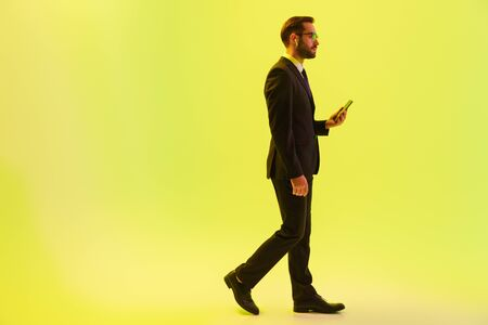 Photo for Handsome young businessman wearing formal suit walking isolated over yellow background, using wireless earphones and holding mobile phone - Royalty Free Image