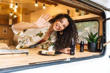 Photo pour Beautiful young brunette woman standing inside a trailer, having lunch, waving hand - image libre de droit