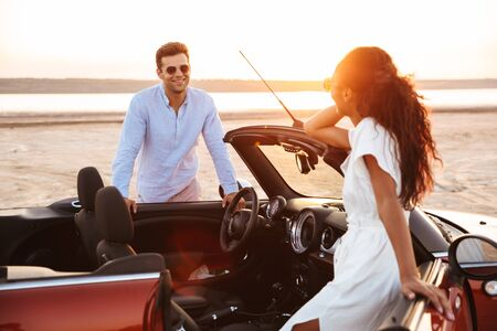 Photo for Image of gorgeous multiethnic couple man and woman smiling while standing by car at seaside - Royalty Free Image