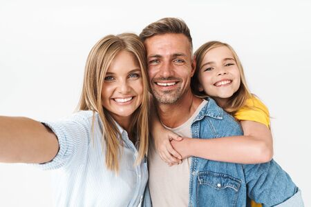 Foto de Image of amusing caucasian family woman and man with little girl smiling and taking selfie photo together isolated over white background - Imagen libre de derechos