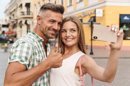 Photo pour Photo of young happy couple in summer clothes smiling and showing thumb up while taking selfie photo on city street - image libre de droit
