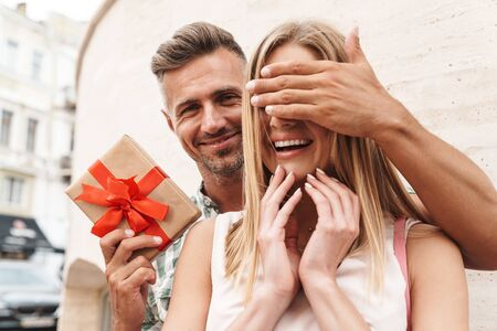Photo pour Image of charming excited couple in summer clothes smiling and holding present box together while standing against wall on city street - image libre de droit
