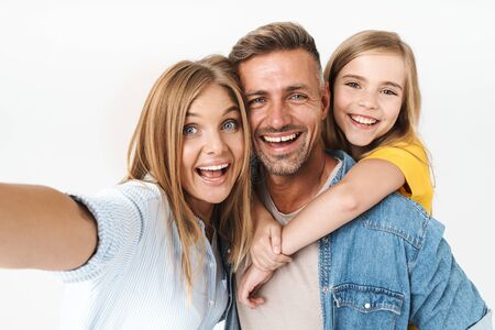 Photo pour Image of adorable caucasian family woman and man with little girl smiling and taking selfie photo together isolated over white background - image libre de droit