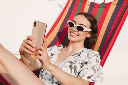 Photo pour Image of a cheerful young pretty woman at the beach posing on a hammock take a selfie by mobile phone. - image libre de droit