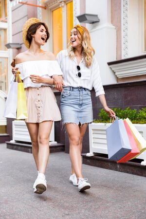 Photo pour Image of a happy laughing optimistic happy young girls friends walking by street outdoors holding shopping bags. - image libre de droit