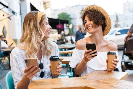 Photo pour Photo of a happy young optimistic girls friends sitting outdoors in cafe drinking coffee using mobile phones. - image libre de droit