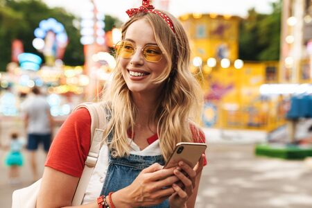 Photo for Image of a smiling young cheery blonde woman in amusement park using mobile phone. - Royalty Free Image