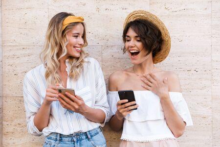 Photo pour Image of a smiling surprised pleased happy positive young women friends outdoors using mobile phones chatting. - image libre de droit