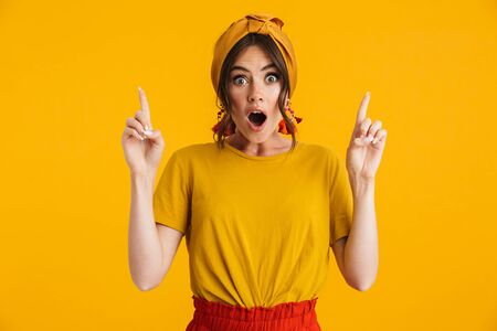 Photo pour Portrait of a pretty excited young girl casually dressed standing isolated over yellow background, pointing fingers at copy space - image libre de droit