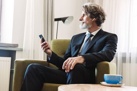 Photo for Photo of a serious concentrated bearded mature grey-haired businessman posing indoors at home sitting on chair near window dressed in formal clothes using mobile phone. - Royalty Free Image