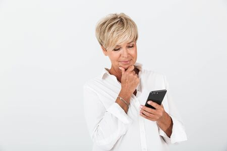 Foto per Portrait closeup of gorgeous adult woman with short blond hair thinking and holding cellphone isolated over white background in studio - Immagine Royalty Free