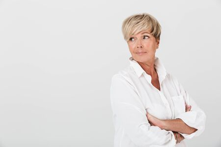 Foto per Portrait of caucasian adult woman looking at copyspace with arms crossed isolated over white background in studio - Immagine Royalty Free