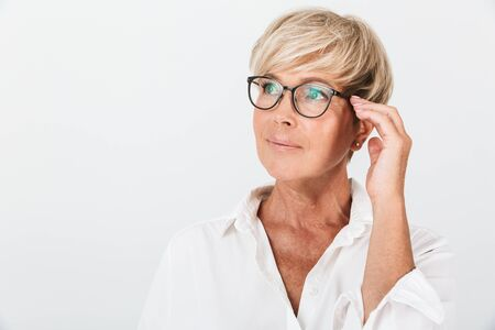 Photo pour Portrait of beautiful adult woman looking aside and touching her eyeglasses isolated over white background in studio - image libre de droit