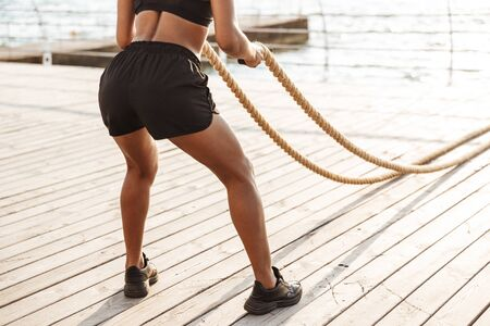 Photo pour Cropped image of muscular young woman in sportive clothes doing workout with battle ropes by seaside in morning - image libre de droit