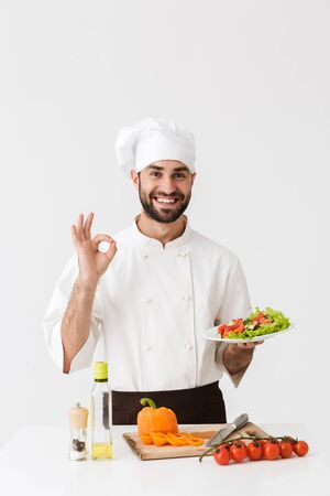 Photo pour Image of young cook man in uniform showing ok sign and holding plate with vegetable salad isolated over white wall - image libre de droit