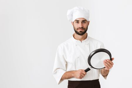 Photo pour Image of handsome chief man in cook uniform looking at camera and holding frying pan isolated over white wall - image libre de droit