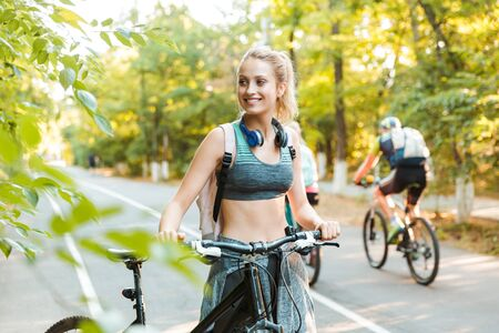 Photo pour Cheerful young fitness girl carrying backpack, wearing sports clothing walking with a bicycle at the park - image libre de droit