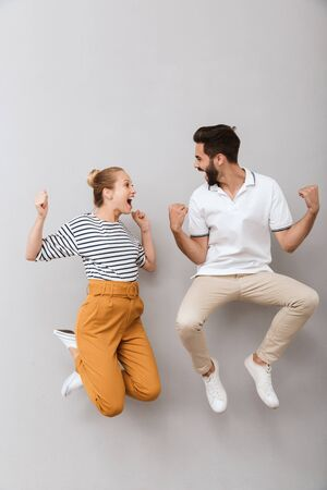 Photo for Image of a young emotional happy loving couple friends man and woman jumping indoors isolated over grey background make winner gesture. - Royalty Free Image