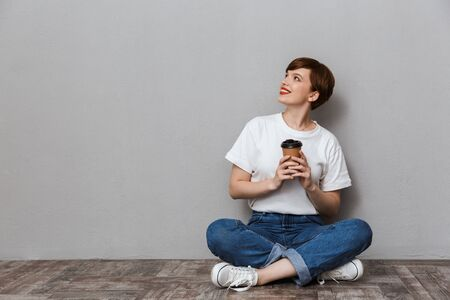 Photo pour Image of gorgeous woman looking aside while sitting on floor with takeaway coffee cup isolated over gray background - image libre de droit