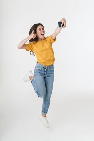 Foto de Image of a positive optimistic young emotional woman jumping isolated over white wall background take a selfie by mobile phone showing thumbs up. - Imagen libre de derechos