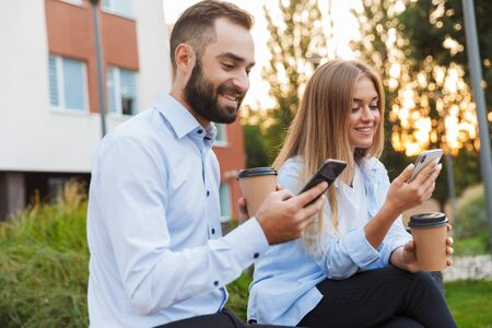 Photo pour Image of a young happy colleagues man and woman businesspeople sit outside at the street using mobile phones. - image libre de droit