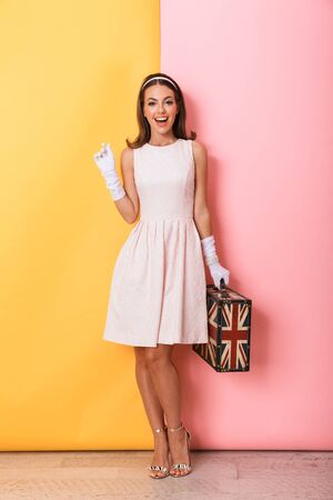 Photo pour Full length of a beautiful young elegant brunette woman wearing dress and gloves standing isolated over double color background, carrying suitcase - image libre de droit