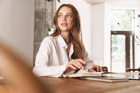 Photo pour Photo of a concentrated young beautiful business woman sit indoors in office using laptop computer holding notebook. - image libre de droit