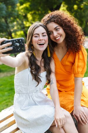 Photo pour Two cheerful young girls friends wearing summer dresses spending time outdoors at the city park, taking a selfie while sitting on a bench - image libre de droit