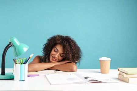 Photo pour Beautiful smiling young african businesswoman casually dressed sleeping while sitting at the desk isolated over blue background - image libre de droit
