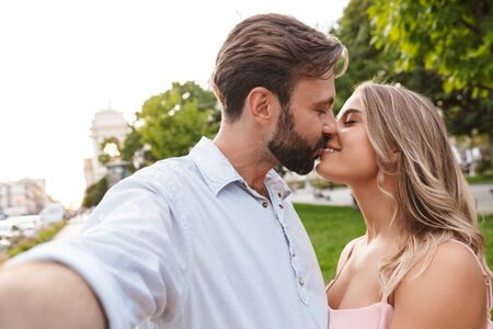 Photo pour Image of a happy amazing young loving couple walking by street outdoors take a selfie by camera kissing. - image libre de droit