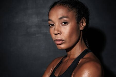 Photo pour Image closeup of young african american woman in sportswear standing isolated over black background - image libre de droit