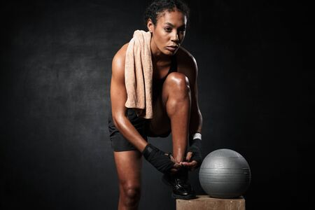 Foto für Image of attractive african american woman in boxing hand wraps tying her sneakers laces by fitness ball isolated over black background - Lizenzfreies Bild