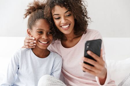 Photo for Image of satisfied african american woman and her little daughter using cellphone together on sofa at home - Royalty Free Image