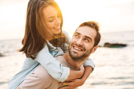 Photo for Image of young happy man giving piggyback ride and looking at beautiful woman while walking on sunny beach - Royalty Free Image
