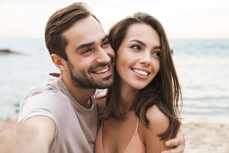 Photo pour Photo of smiling young couple hugging and taking selfie photo while resting on sunny beach - image libre de droit