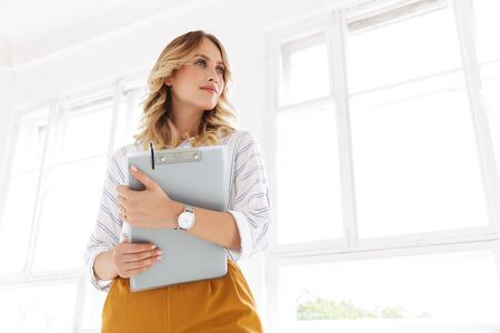 Foto de Image of successful elegant secretary woman holding clipboard in white office - Imagen libre de derechos