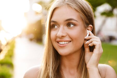 Photo for Close up of a smiling beautiful young blonde girl listening to music with earphones while standing outdoors - Royalty Free Image