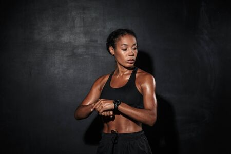 Photo for Attractive muscular young african sportswoman standing isolated over black background, checking time - Royalty Free Image