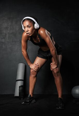 Photo for Confident young african fitness woman resting after workout with gym equipment isolated over black background, listening to music with wireless headphones - Royalty Free Image