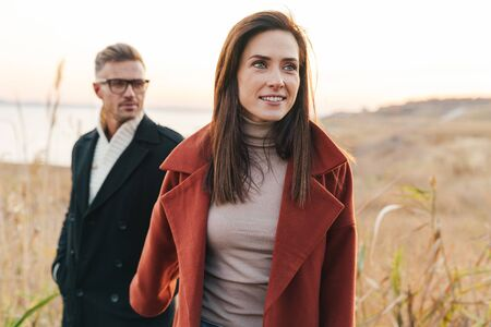 Photo for Close up of a beautiful smiling couple wearing autumn clothing walking outdoors at the seaside - Royalty Free Image