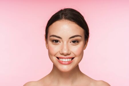 Photo pour Beauty portrait of a beautiful smiling young topless brunette woman standing isolated over pink background - image libre de droit